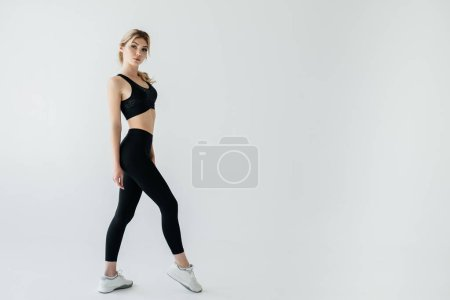 side view of young blond sportswoman in black sportswear posing isolated on grey