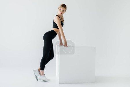 side view of sportive woman in black sportswear standing near white cube on grey background