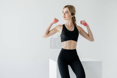 portrait of attractive woman in black sportswear with dumbbells sitting on white cube on grey backdrop