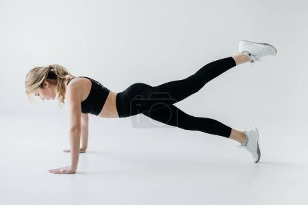 side view of young sportswoman doing push ups isolated on grey