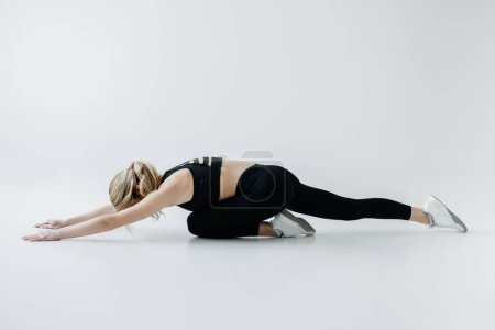 Photo for Side view of young sportswoman in black sportswear stretching isolated on grey - Royalty Free Image