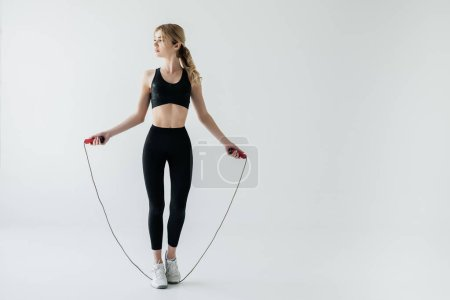 young sportive woman with skipping rope isolated on grey