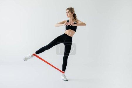 Photo pour Jeune femme athlétique avec bande en caoutchouc sur pieds isolés sur fond gris - image libre de droit