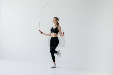 young sportive woman exercising with skipping rope isolated on grey