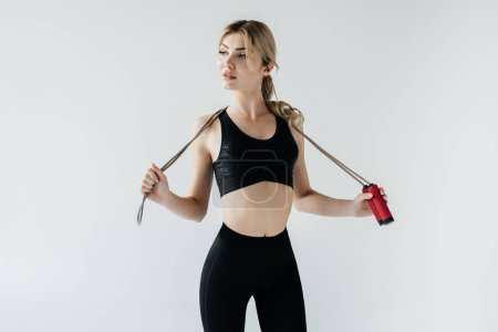 portrait of young sportive woman with skipping rope isolated on grey
