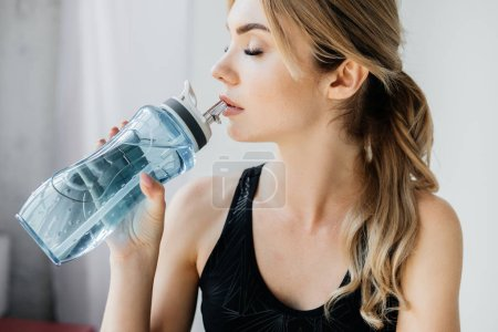 Photo for Side view of athletic woman drinking water from sportive water bottle on grey backdrop - Royalty Free Image