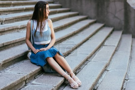 Photo for Beautiful smiling young woman in eyeglasses sitting on stairs and looking away - Royalty Free Image