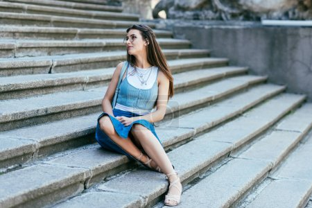 Photo for Beautiful pensive young woman in eyeglasses sitting on stairs and looking away - Royalty Free Image