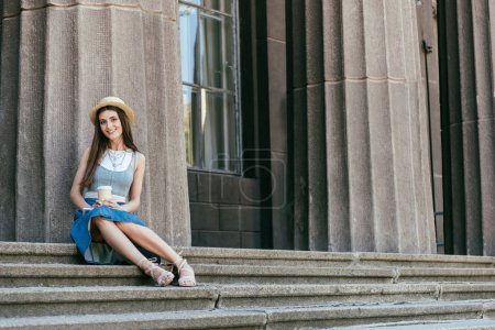 Photo for Beautiful smiling girl holding digital tablet and coffee to go while sitting on stairs - Royalty Free Image
