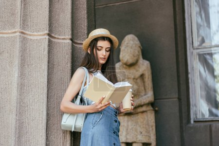 beautiful girl in hat holding paper cup and reading book near column