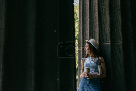 beautiful smiling young woman with book and coffee to go standing between columns and looking away