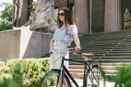 Photo for Girl in sunglasses looking away while standing with bicycle near beautiful building with columns and stairs - Royalty Free Image