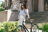 girl in sunglasses looking away while standing with bicycle near beautiful building with columns and stairs