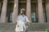 low angle view of girl in sunglasses looking away while standing with bicycle near beautiful building with columns and stairs