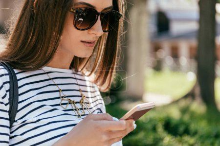 close-up view of beautiful girl in sunglasses using smartphone on street