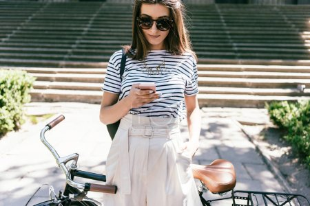 Photo for Attractive smiling young woman in sunglasses using smartphone while standing with bicycle on street - Royalty Free Image