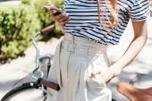 """Постер, картина, фотообои """"Обрезанный снимок девушка с помощью смартфона стоя с велосипедов на улице"""""""