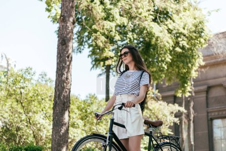 low angle view of beautiful girl in sunglasses riding bicycle on street