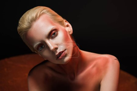 beautiful young nude woman with red makeup posing for fashion shoot on black