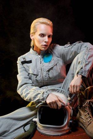 Photo pour Attrayant femme astronaute en scaphandre tenant casque et assis sur la planète - image libre de droit