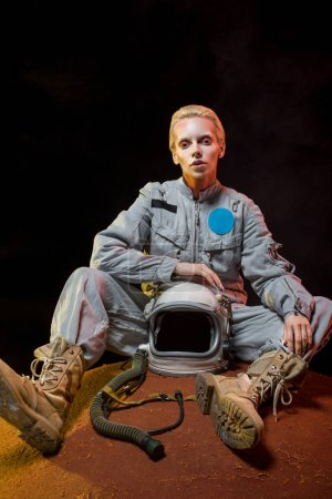 beautiful female cosmonaut in spacesuit holding helmet and sitting on planet