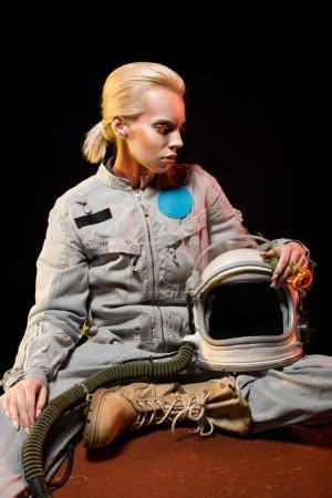 Photo pour Belle femme cosmonaute en combinaison spatiale et casque assis sur la planète - image libre de droit