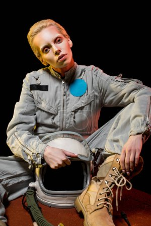 fashionable female astronaut in spacesuit and helmet sitting on planet