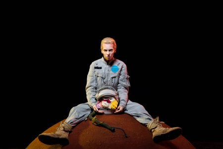 attractive female astronaut in spacesuit with flowers in helmet sitting on planet