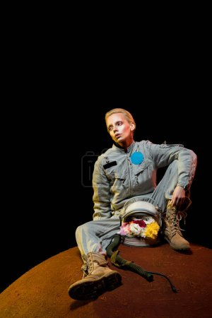 beautiful astronaut in spacesuit with flowers in helmet sitting on planet