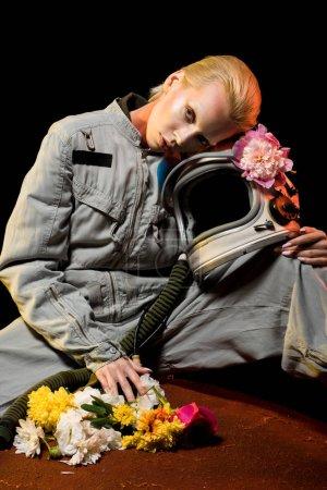 Photo pour Caucasien astronaute en scaphandre avec fleurs et un casque assis sur la planète - image libre de droit