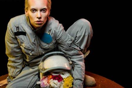 cosmonaut in spacesuit with flowers in helmet sitting on planet