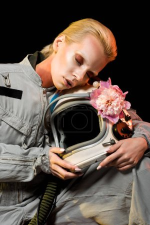 sensual female astronaut in spacesuit with peony flower and helmet, isolated on black