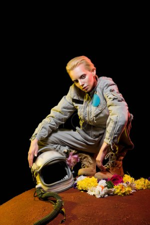stylish cosmonaut in spacesuit with flowers and helmet sitting on planet