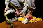 cropped view of astronaut in spacesuit with flowers and helmet sitting on mars