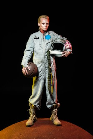 cosmonaut in spacesuit holding basketball ball and helmet with flower while standing on red planet