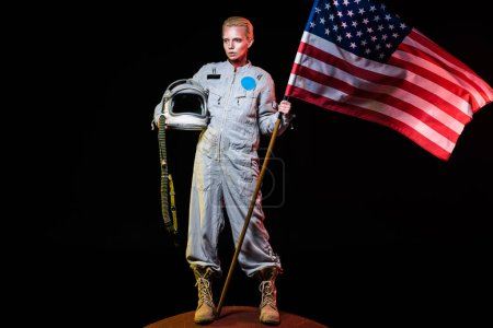 spacewoman in spacesuit holding helmet and american flag on mars