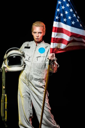 beautiful female cosmonaut in spacesuit holding helmet and usa flag, isolated on black