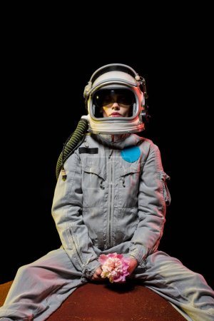 female astronaut in spacesuit and helmet sitting on planet with flower in cosmos