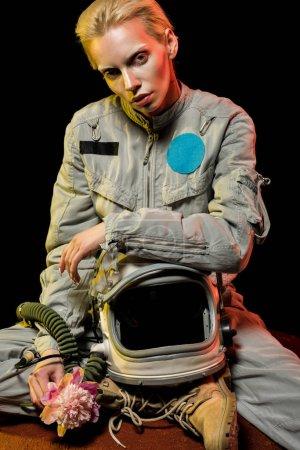Photo pour Séduisante jeune astronaute en scaphandre à casque et pivoine assis sur la planète - image libre de droit