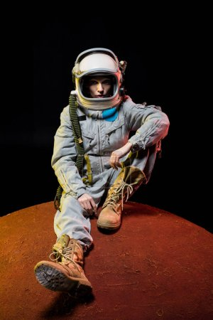young cosmonaut in spacesuit with helmet sitting on planet in space