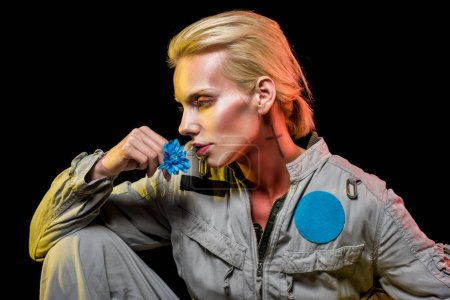 beautiful female cosmonaut posing in spacesuit with blue flower, isolated on black