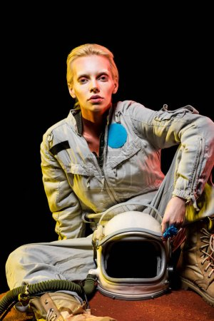 attractive astronaut in spacesuit with helmet sitting on planet