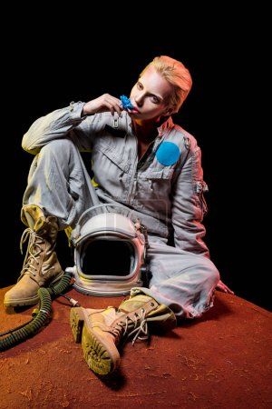 beautiful astronaut in spacesuit with flower and helmet sitting on planet