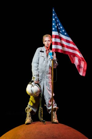 attractive female astronaut in spacesuit holding helmet and american flag on planet