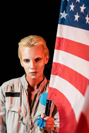 attractive female astronaut in spacesuit holding american flag, isolated on black