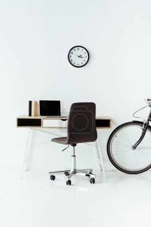 Photo pour Lieu de travail moderne avec ordinateur portable et vélo devant le mur blanc - image libre de droit