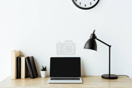 Photo for Laptop with blank screen on work desk in front of white wall - Royalty Free Image