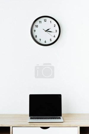 laptop on work desk under clock hanging on white wall