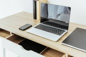laptop with smartphone and books on work desk at office