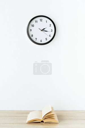 old book on wooden tabletop in front of white wall with hanging clock